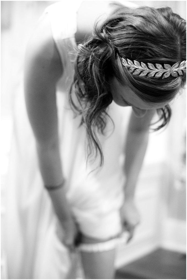 bride putting on garter wedding photo