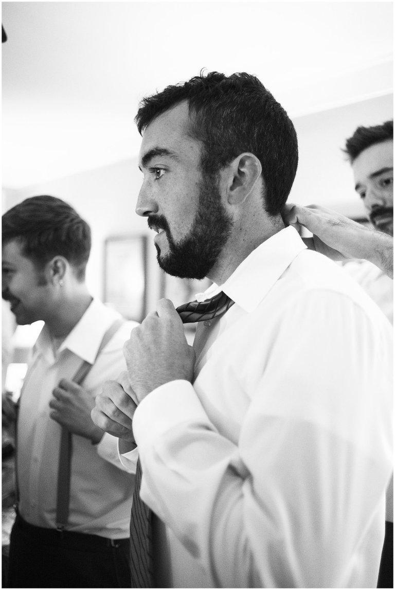 groom tying tie photo