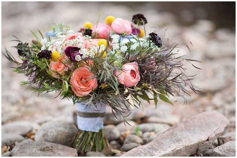 Love Letter Floral bridal bouquet on river rocks wedding photo