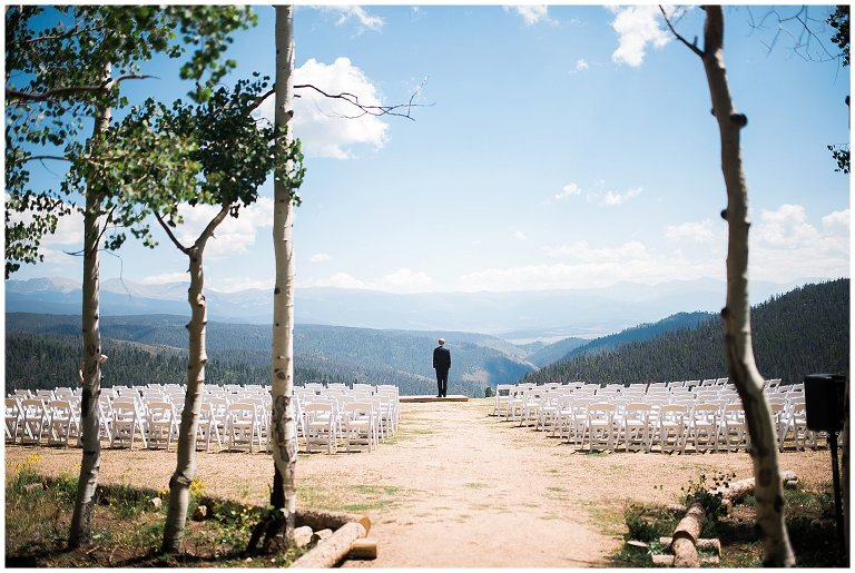 groom at top of colorado mountain first look photo