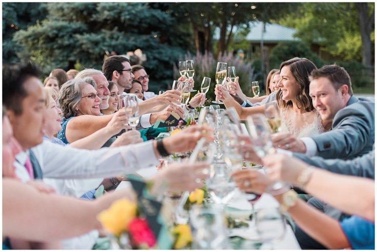 guest cheersing at al fresco wedding photo