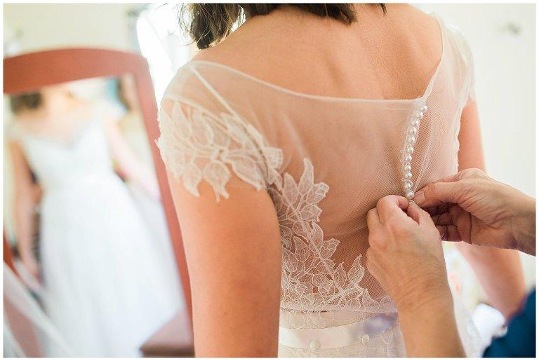 mom buttoning bride's dress at Colorado farm wedding photo