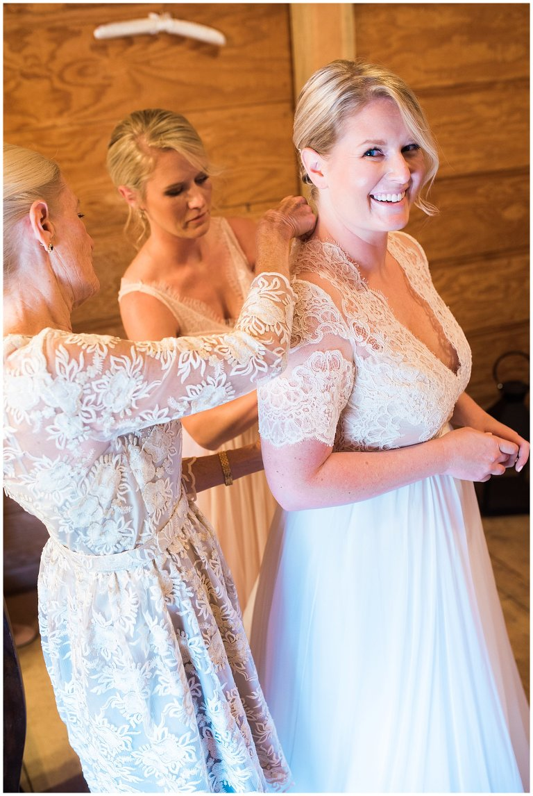 bride getting dressed with help of mother and sister photo