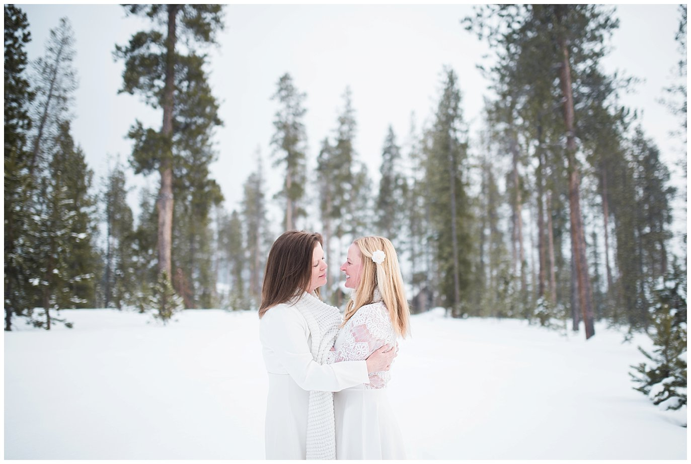 two brides cuddle in evergreen trees at Winter Devil's Thumb Ranch Elopement