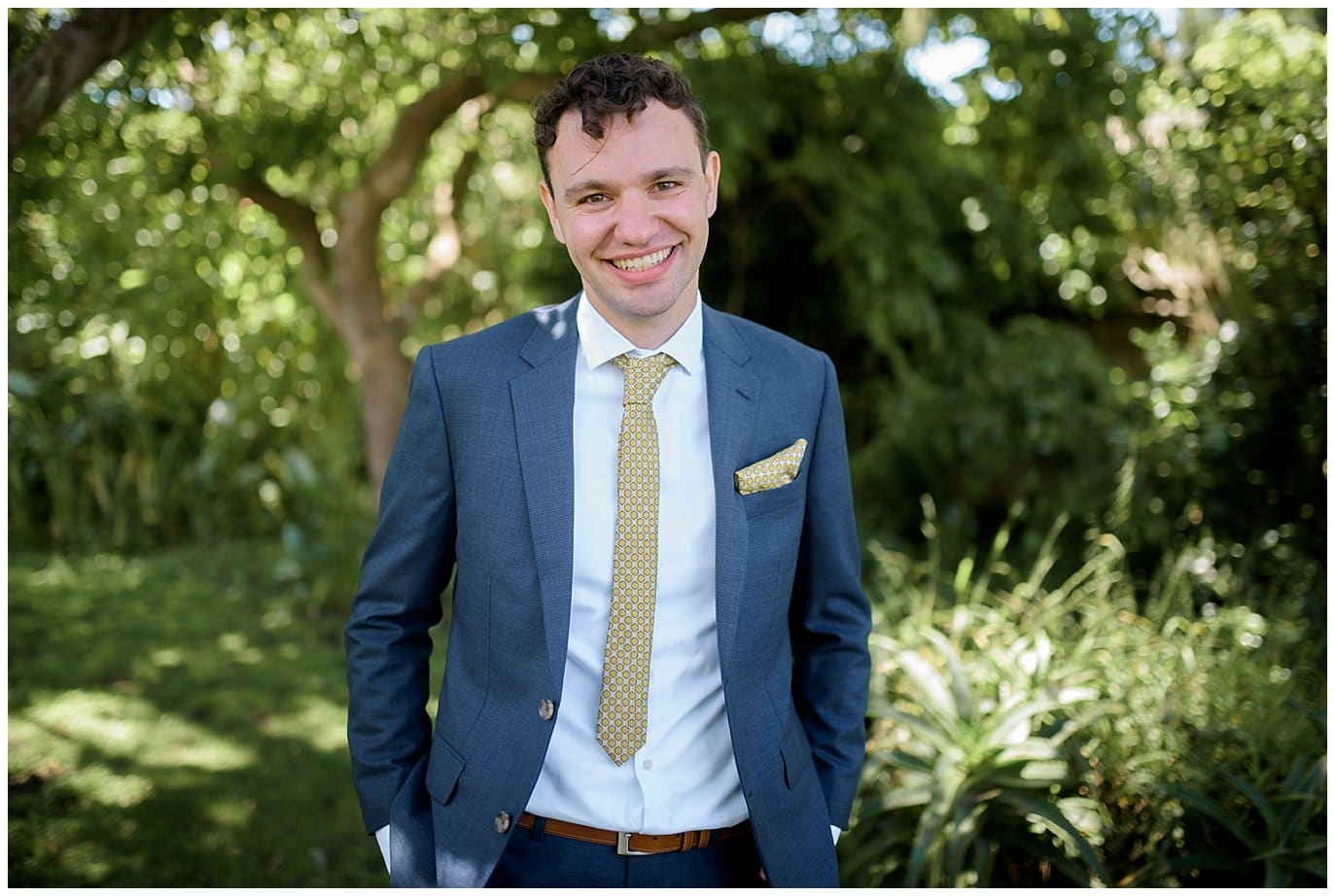 groom in blue suit with yellow tie photo