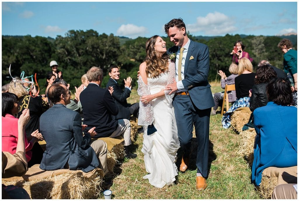 bride and groom walk back down aisle after ceremony at Mann Family Farm wedding by Denver Wedding Photographer Jennie Crate