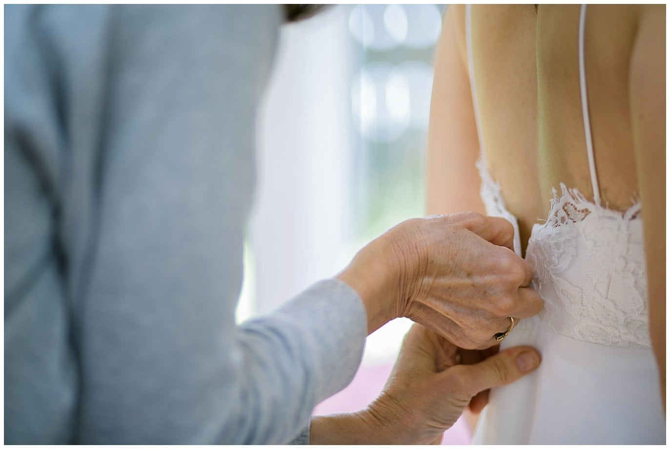 bride getting zipped into dress photo