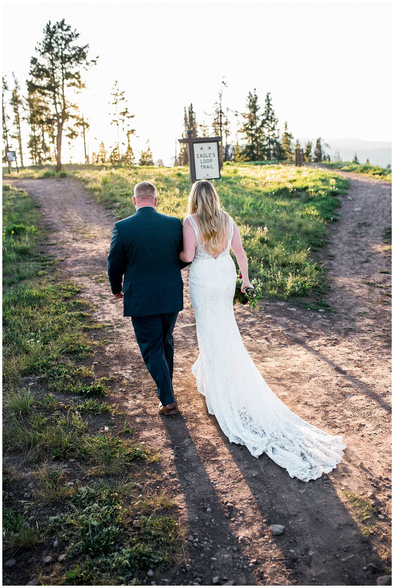 bride and groom walking on mountain at sunset photo