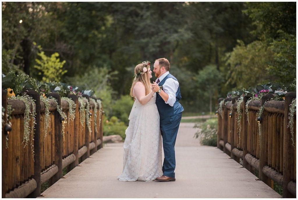 bride and groom dancing on floral bridge photo