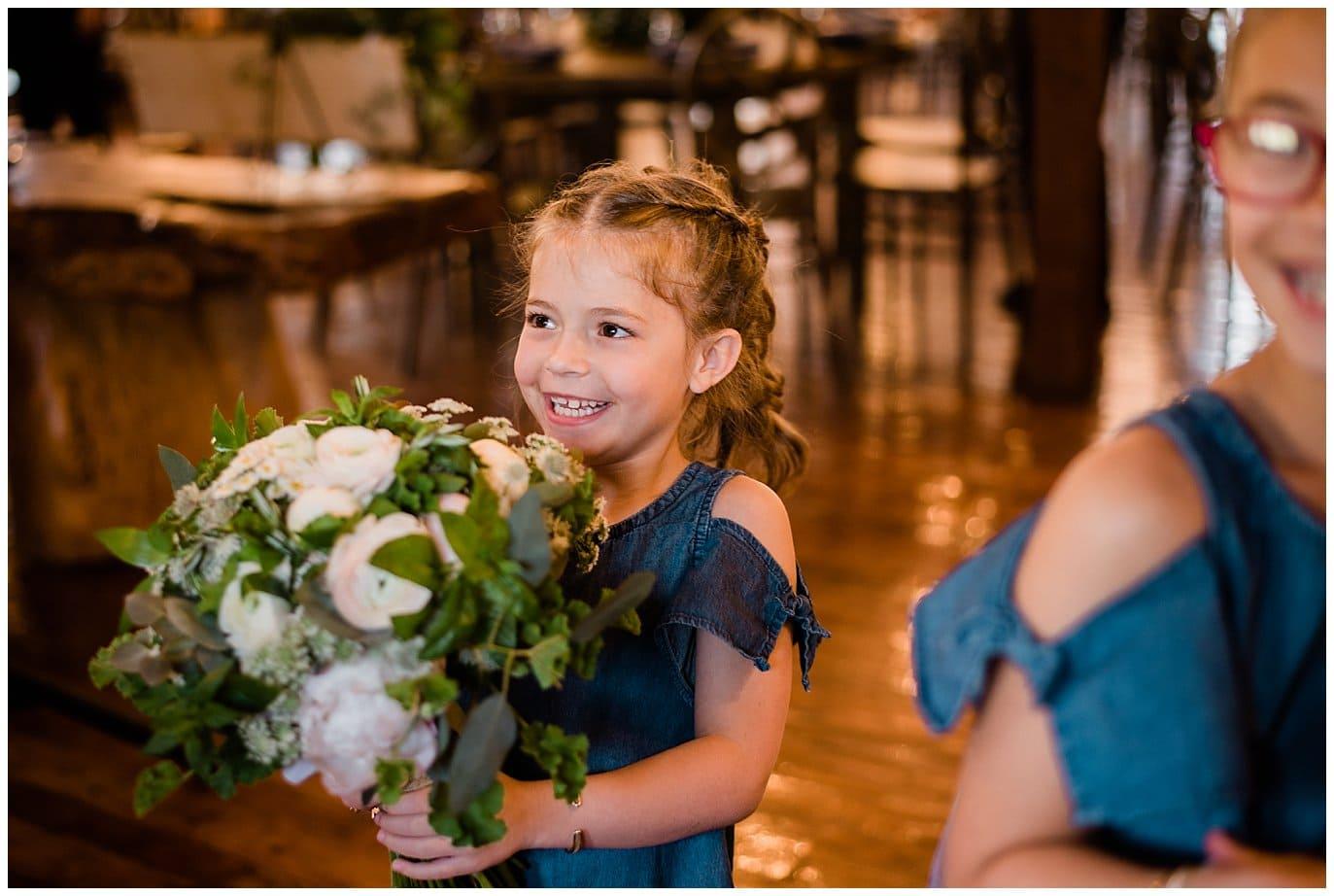 flower girl with bride's flower at Deer Creek Valley Ranch wedding by Denver Wedding Photographer Jennie Crate Photographer