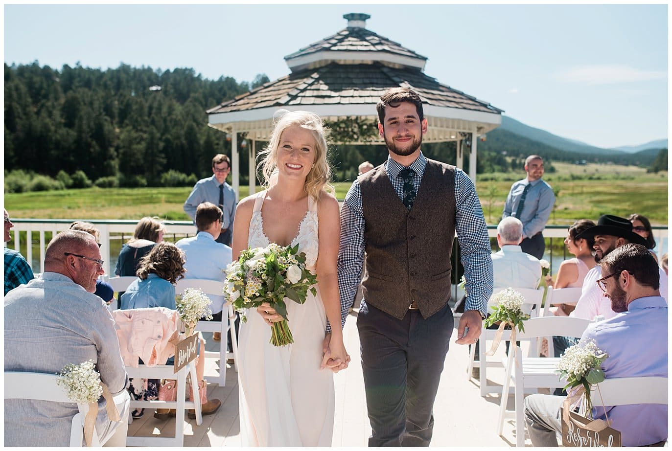 bride and groom walk back down aisle after wedding vows at Deer Creek Valley Ranch wedding by Conifer Wedding Photographer Jennie Crate Photographer