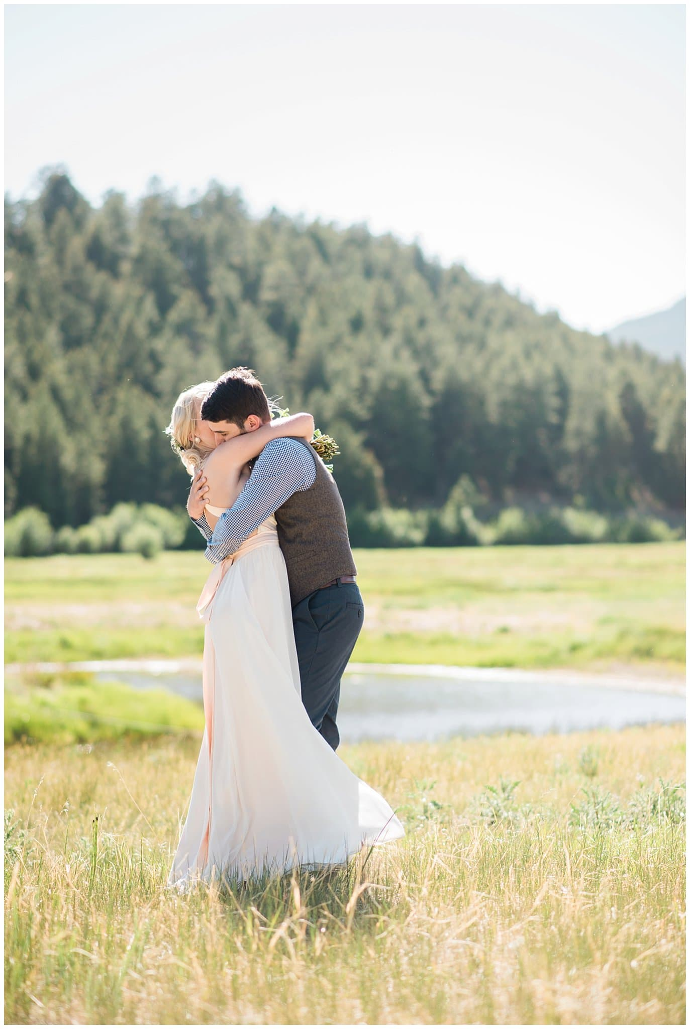 bride and groom in field after ceremony at Deer Creek Valley Ranch wedding by Conifer Wedding Photographer Jennie Crate Photographer
