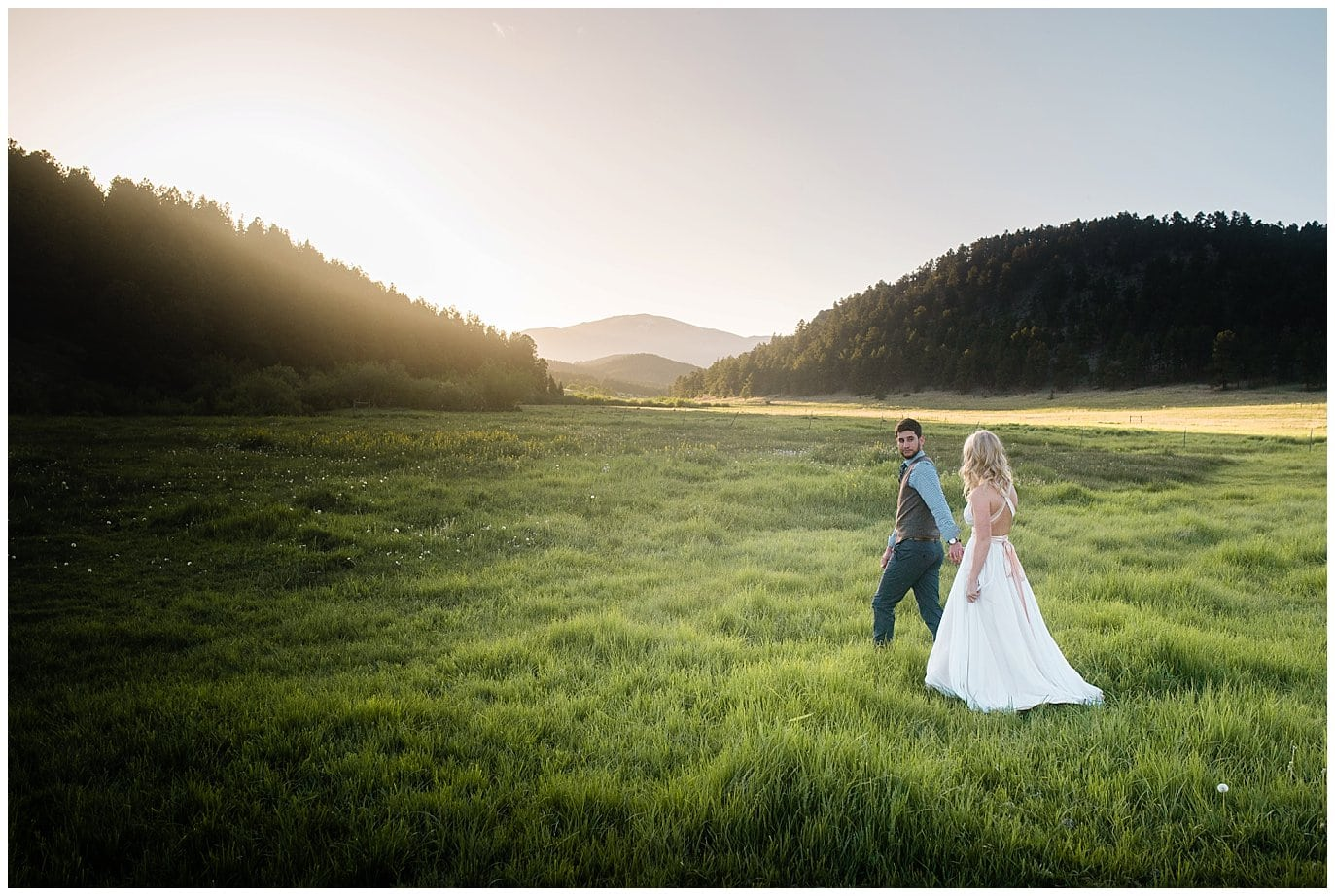 Bride and groom walk in fields at Deer Creek Valley Ranch wedding by Colorado Wedding Photographer Jennie Crate Photographer