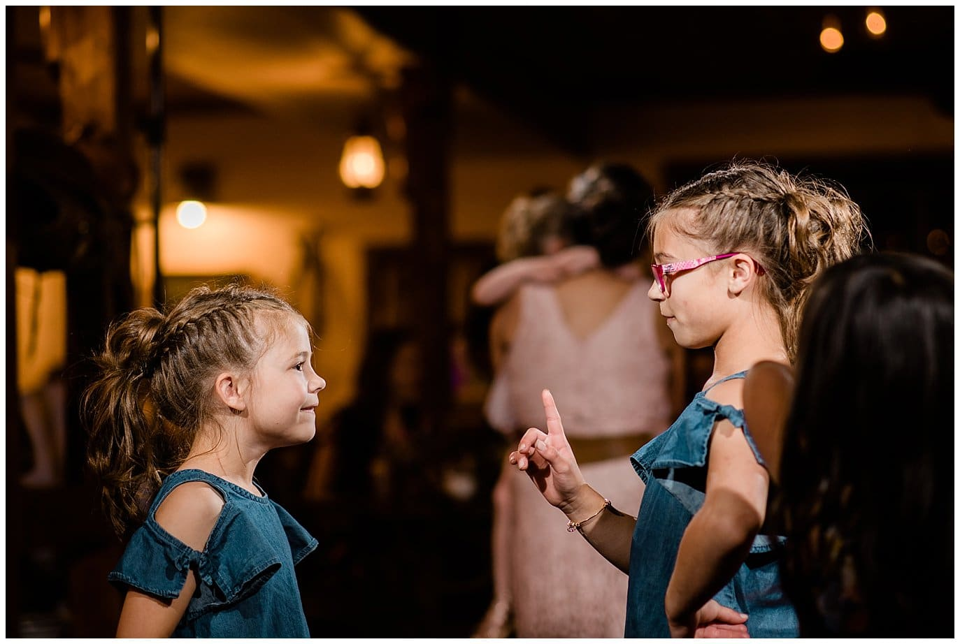 flower girls dance at reception in barn at Deer Creek Valley Ranch wedding by Colorado Wedding Photographer Jennie Crate Photographer