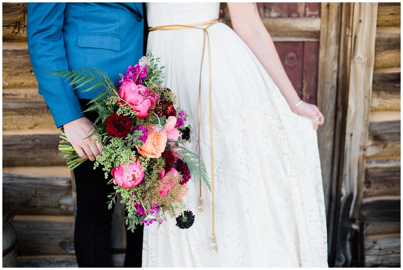 colorful wedding flowers with lace dress and blue suit photo