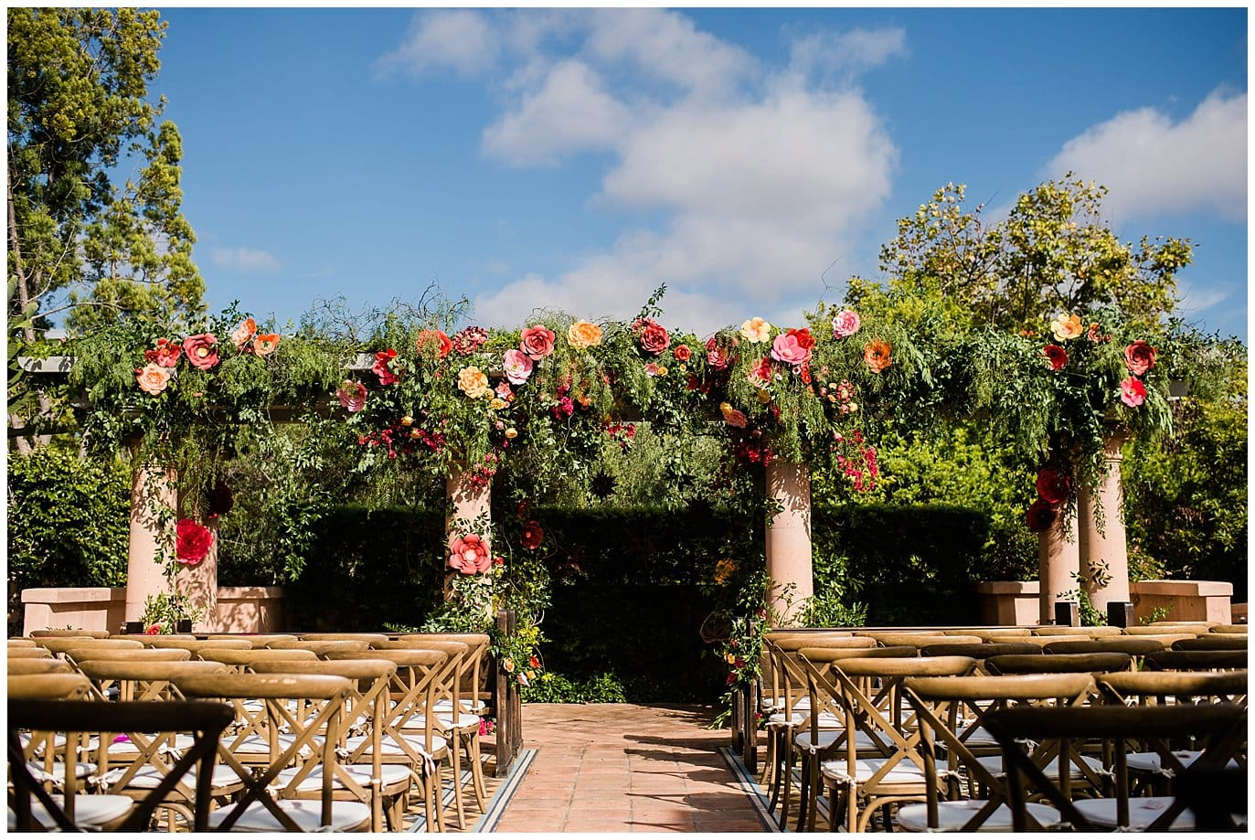 Rancho Valencia Wedding Ceremony on patio with colorful paper flowers photo