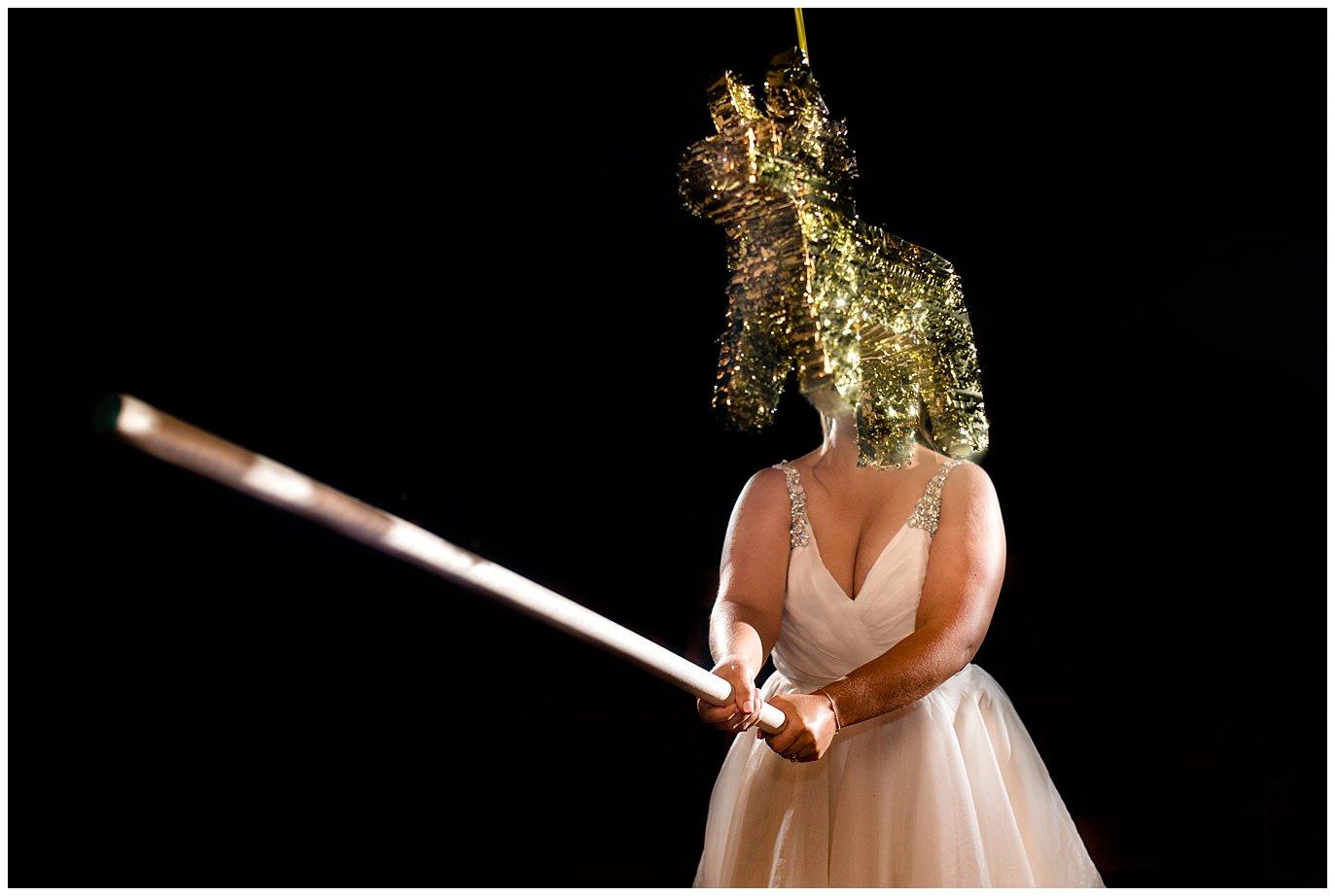 bride smashing wedding unicorn pinata photo