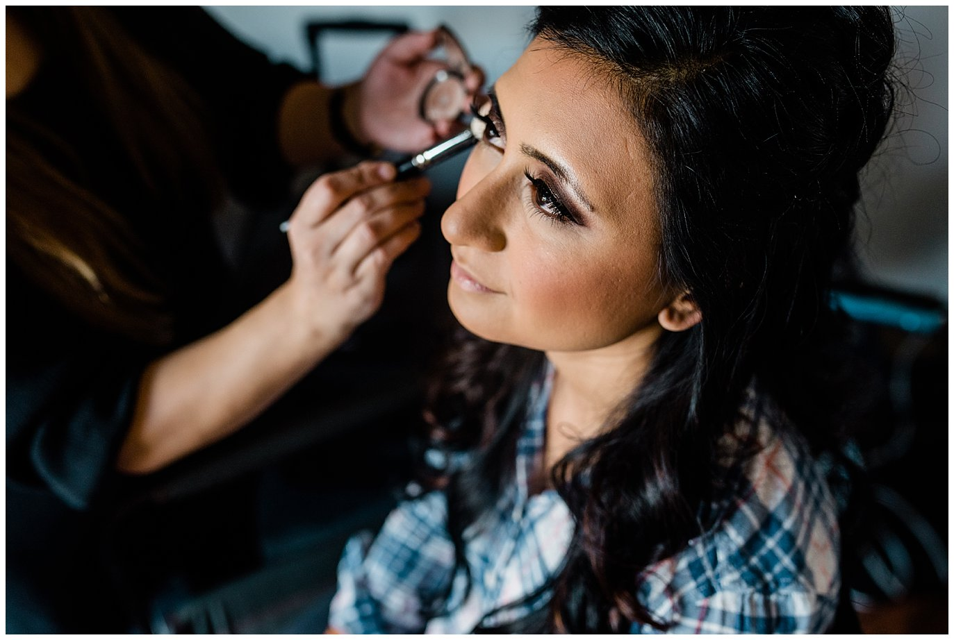 bride getting eye make up on wedding day photo