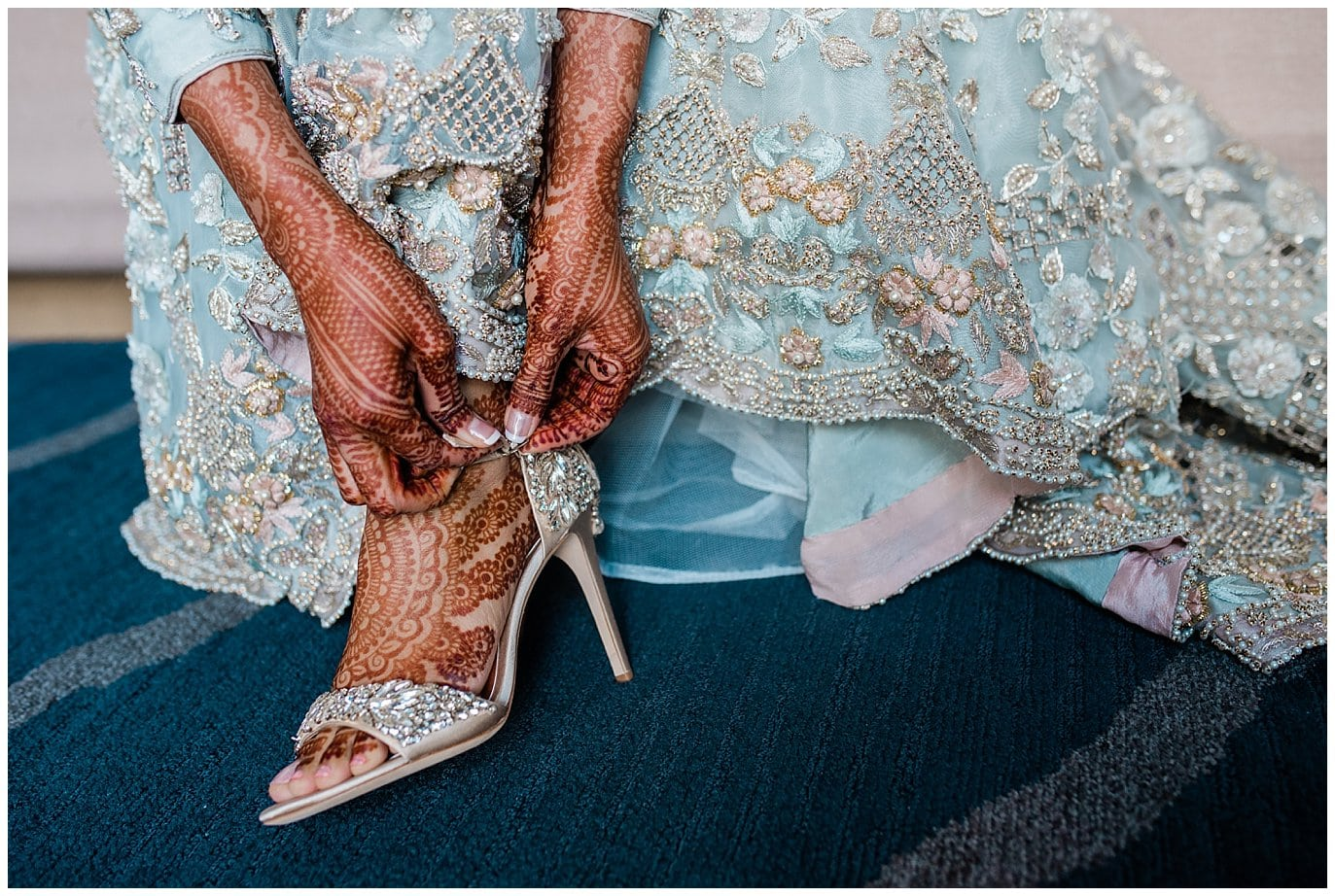 bride putting on heels with henna hands and feet photo
