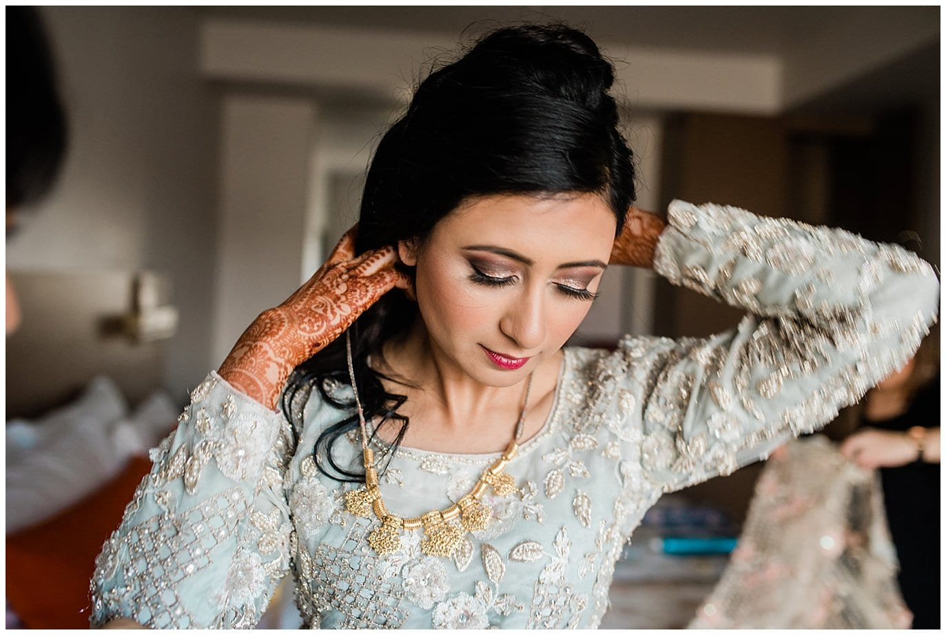 bride putting on gold jewelry before Nikah ceremony photo
