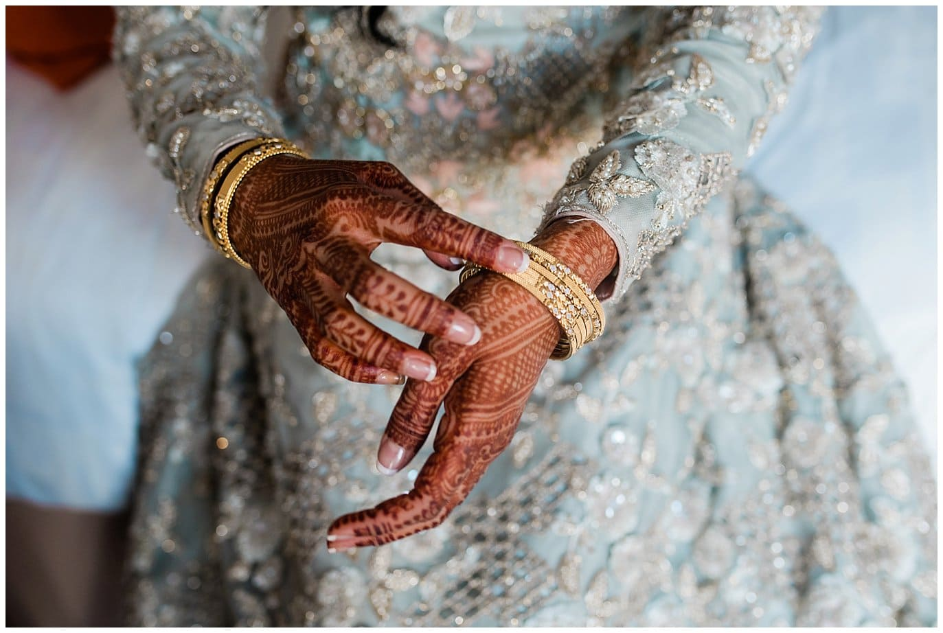 bride putting on gold bracelets with henna photo