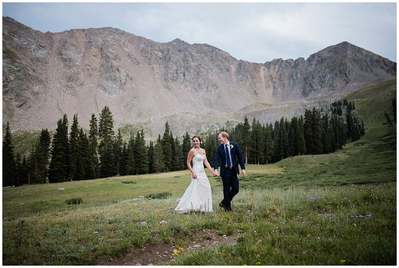 Bride and groom walking in mountains at Arapahoe Basin Black Mountain Lodge Wedding by Arapahoe Basin Wedding Photographer Jennie Crate