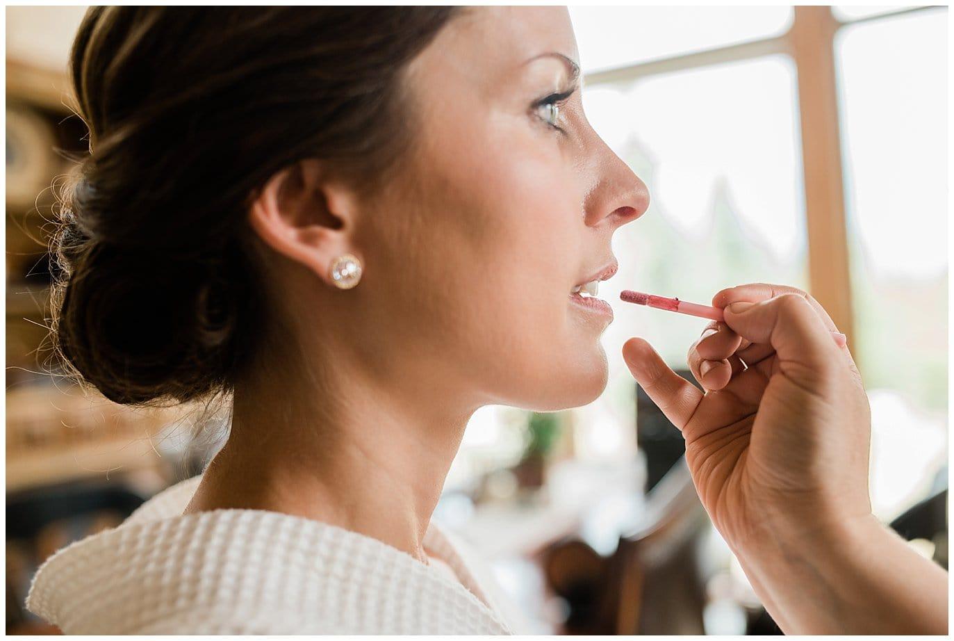 bride getting lipstick put on at Arapahoe Basin Black Mountain Lodge Wedding by Colorado Wedding Photographer Jennie Crate
