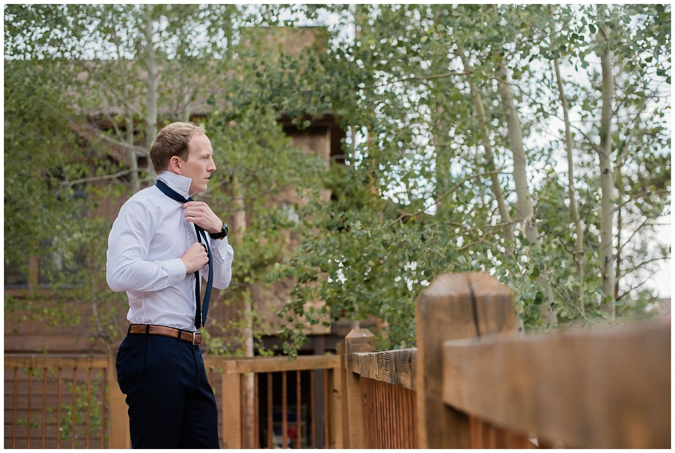 groom getting ready on deck of private home at Arapahoe Basin Black Mountain Lodge Wedding by Keystone Wedding Photographer Jennie Crate