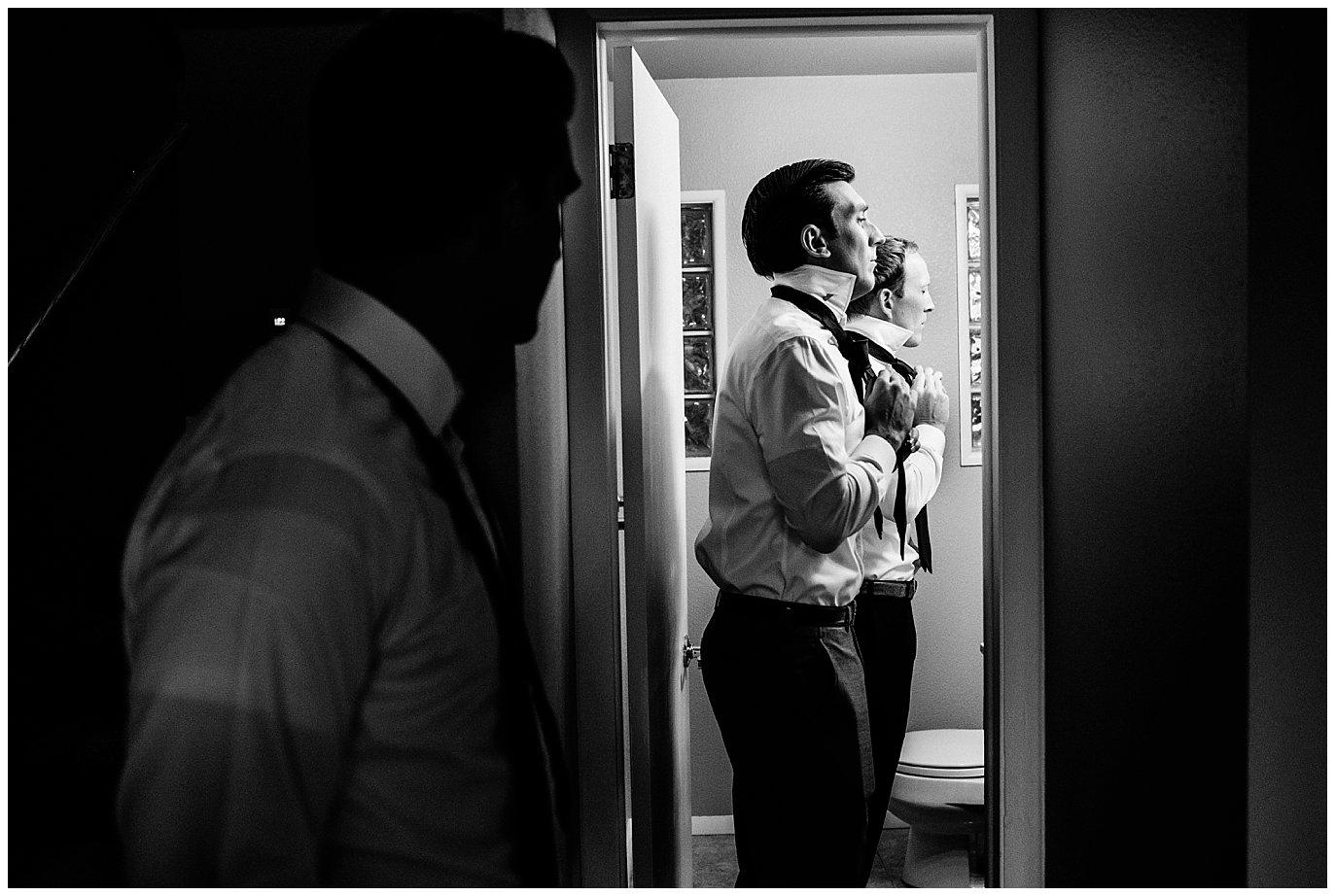 groom and groomsmen tying ties at Arapahoe Basin Black Mountain Lodge Wedding by Arapahoe Basin Wedding Photographer Jennie Crate