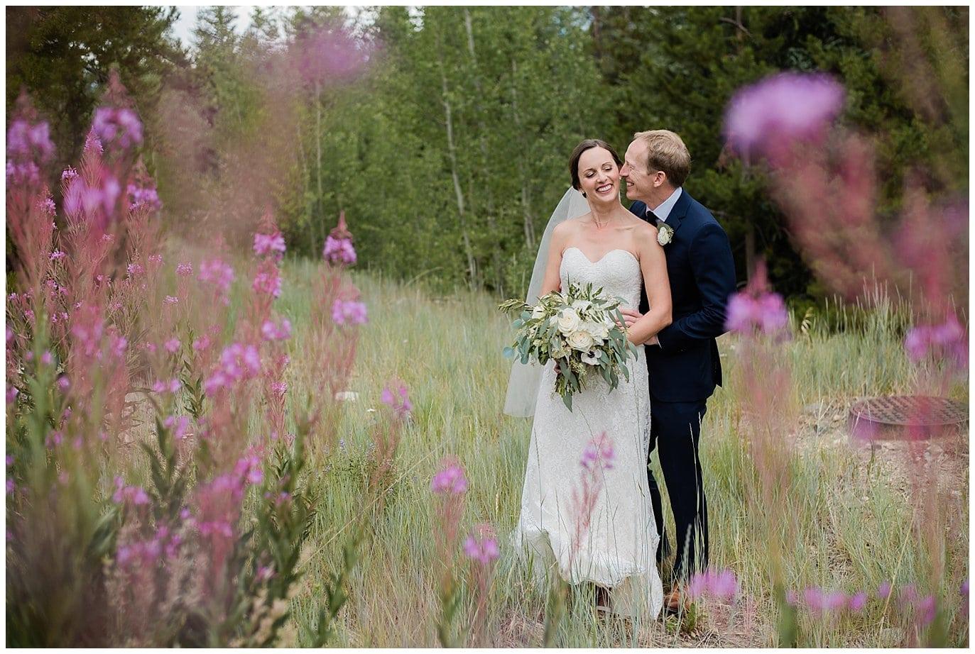 bride and groom portrait with summer purple colorado flowers at Arapahoe Basin Black Mountain Lodge Wedding by Arapahoe Basin Wedding Photographer Jennie Crate