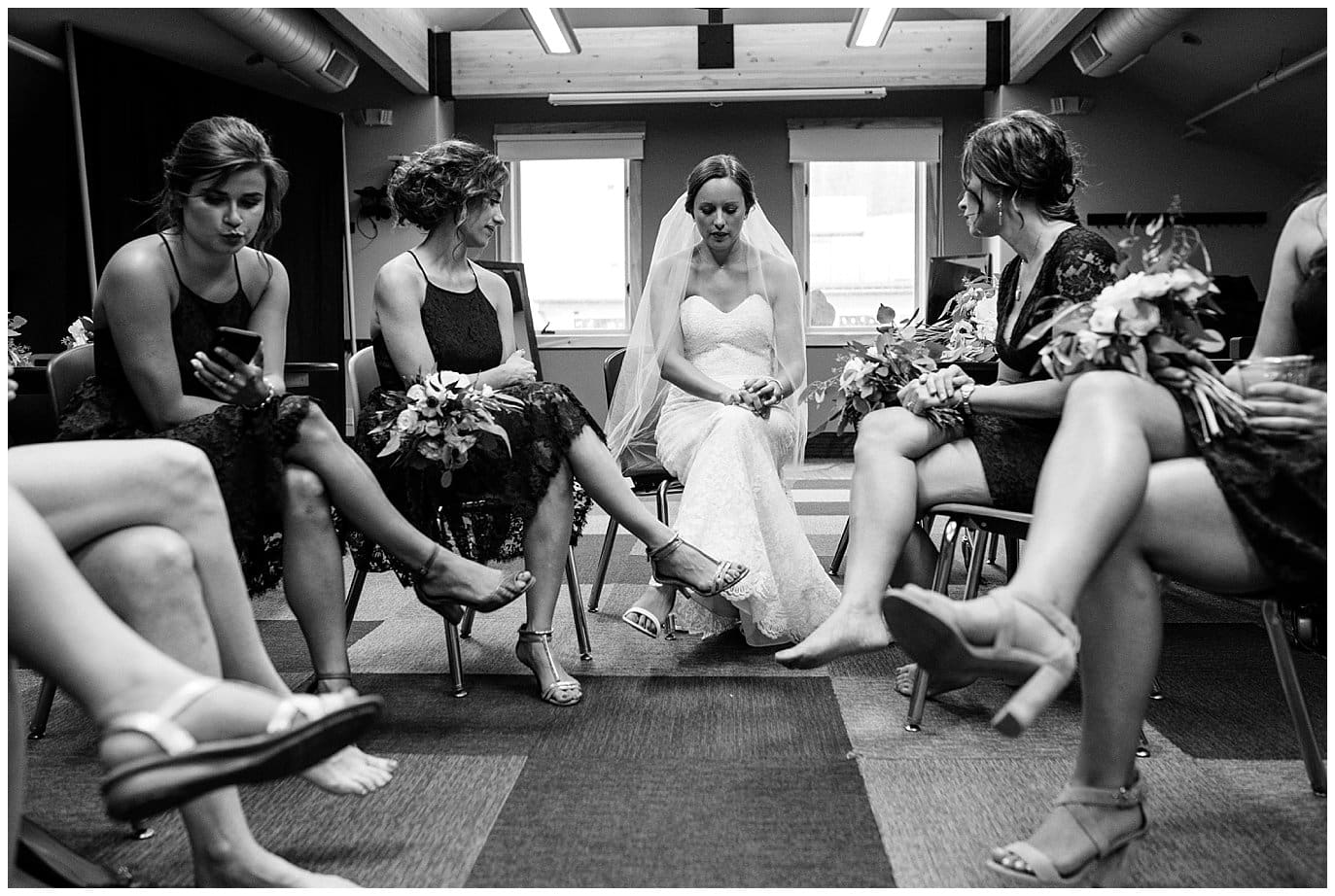 bride and bridesmaid waiting out the rain at Arapahoe Basin Black Mountain Lodge Wedding by Colorado Wedding Photographer Jennie Crate