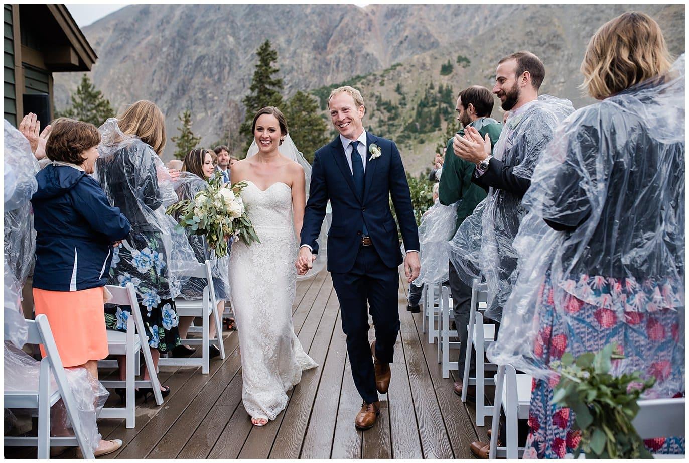 bride and groom walk down aisle at rainy Arapahoe Basin Black Mountain Lodge Wedding by Dillon Wedding Photographer Jennie Crate