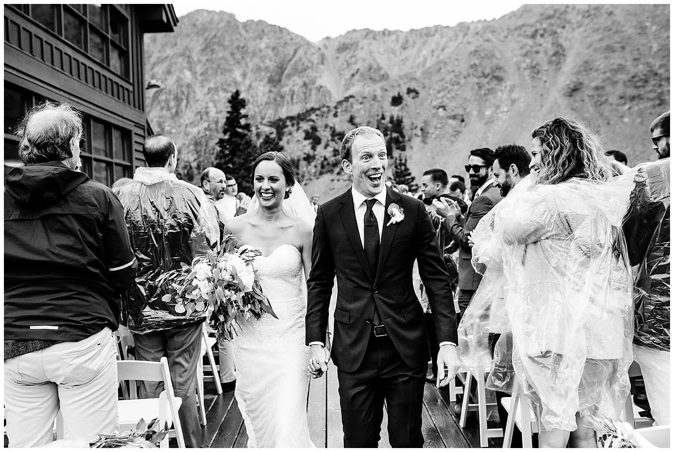 excited bride and groom walk down aisle at rainy Arapahoe Basin Black Mountain Lodge Wedding by Denver Wedding Photographer Jennie Crate