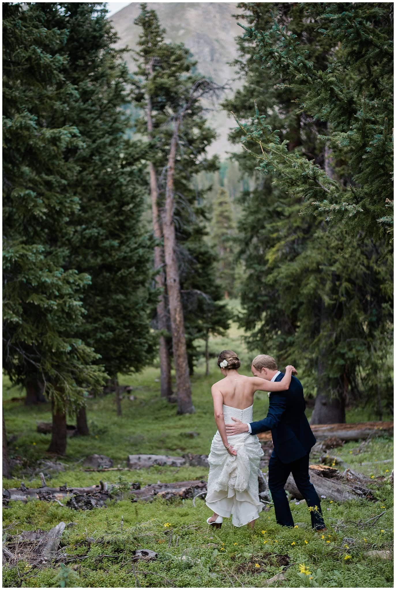 groom helping bride walk in forest at Arapahoe Basin Black Mountain Lodge Wedding by Denver Wedding Photographer Jennie Crate