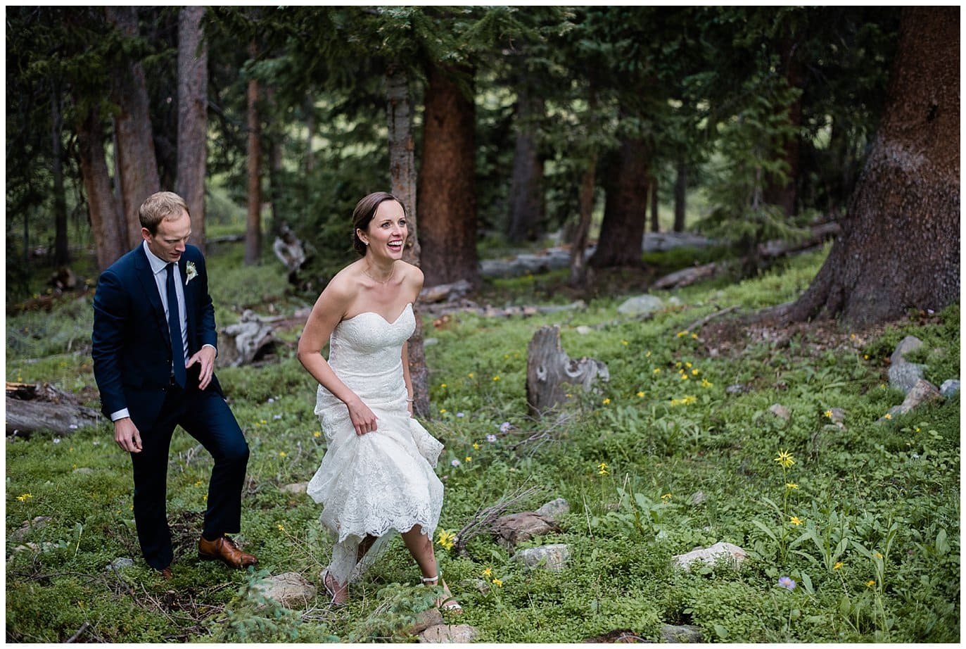 bride and groom walking through lush forests at Black Mountain Lodge wedding photo