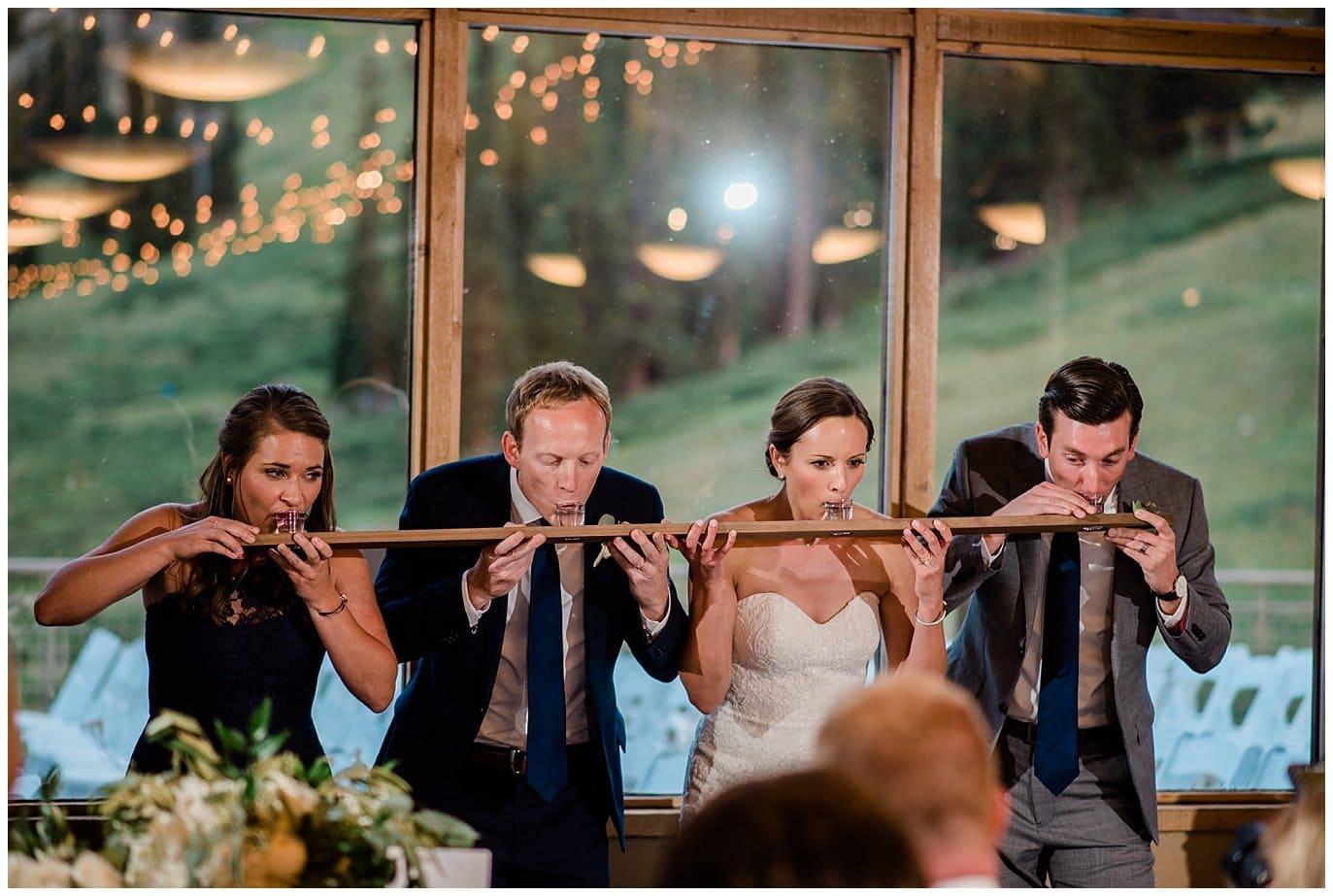 bride and groom do shot ski at colorado mountain wedding photo