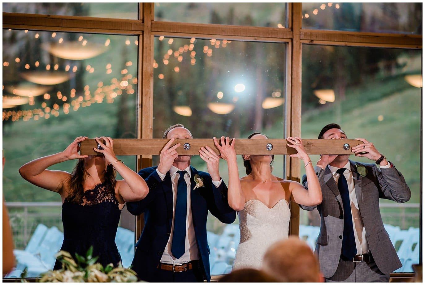 bride and groom do shot ski at Arapahoe Basin Black Mountain Lodge Wedding by Arapahoe Basin Wedding Photographer Jennie Crate