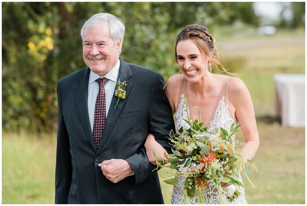 excited bride walks down aisle with father at Winding River Ranch Wedding photo