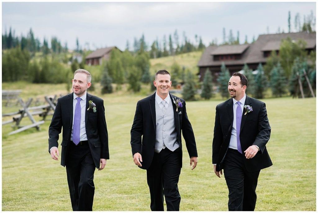 groom and groomsmen walking across lawn for Tabernash wedding photo