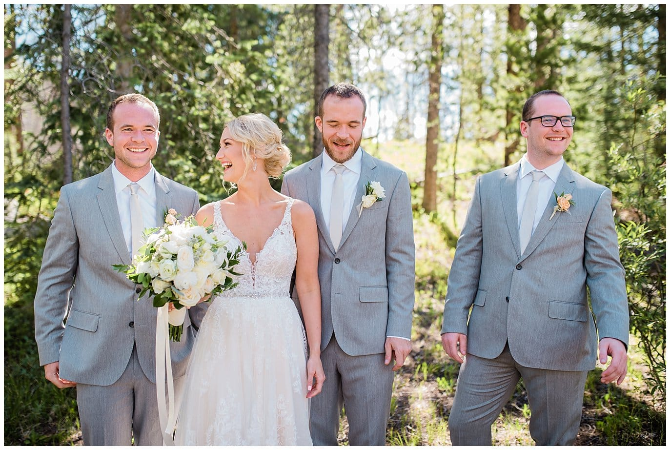 bride in lace dress with groomsmen in grey suits at Summer Piney River Ranch wedding by Vail wedding photographer Jennie Crate, Photographer