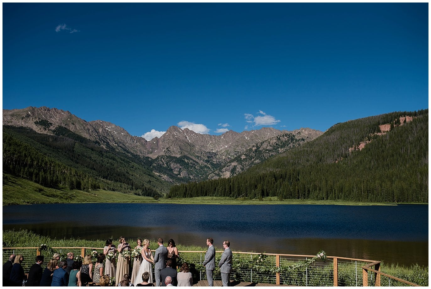 ceremony by lake with blue skies at Elegant Piney River Ranch wedding by Piney River Ranch wedding photographer Jennie Crate, Photographer
