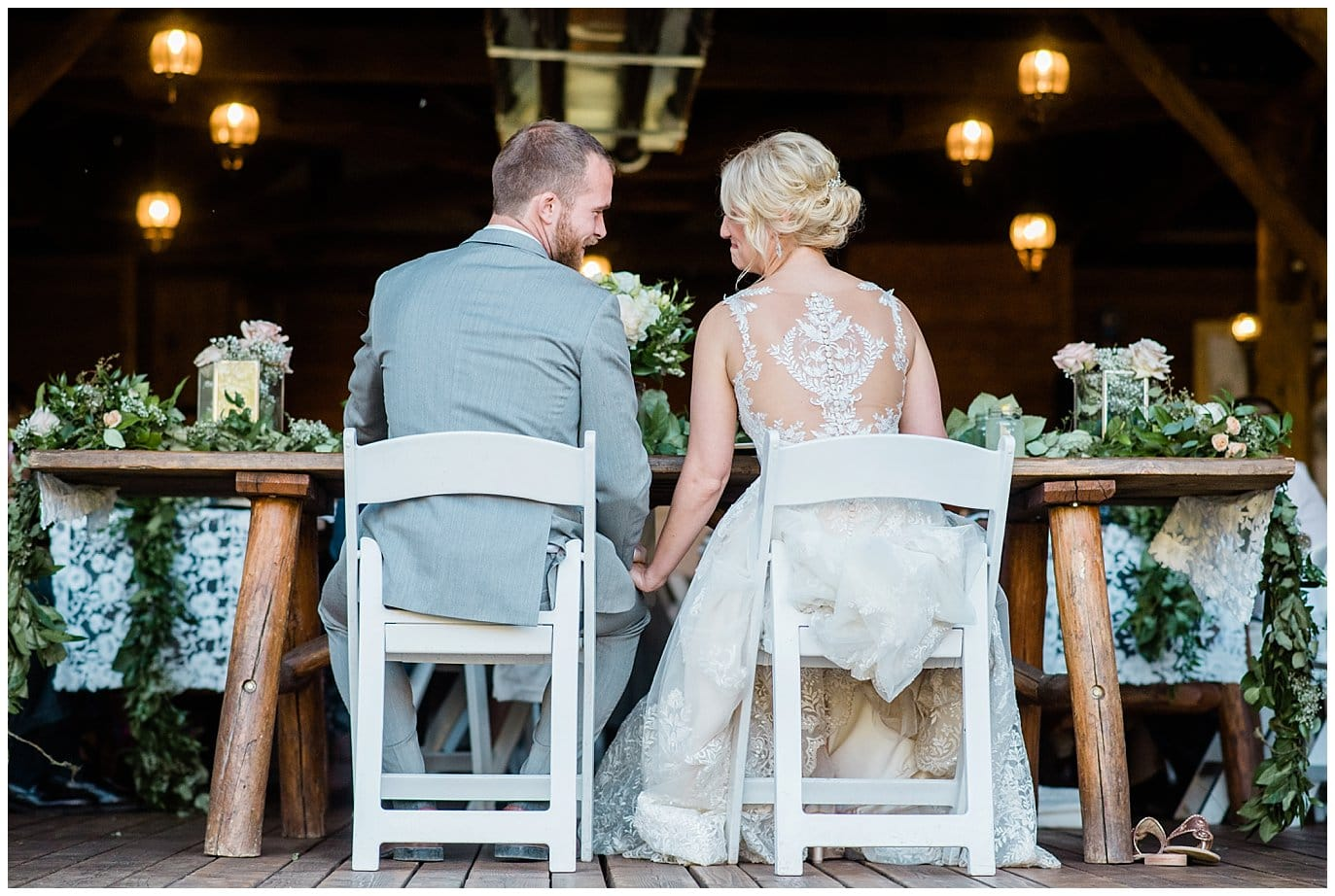 bride and groom hold hands at head table at Piney River Ranch wedding by Vail wedding photographer Jennie Crate, Photographer