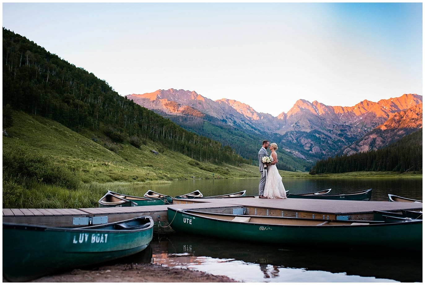 couple at Colorado mountains on pier with canoes at Elegant Piney River Ranch wedding by Piney River Ranch wedding photographer Jennie Crate, Photographer