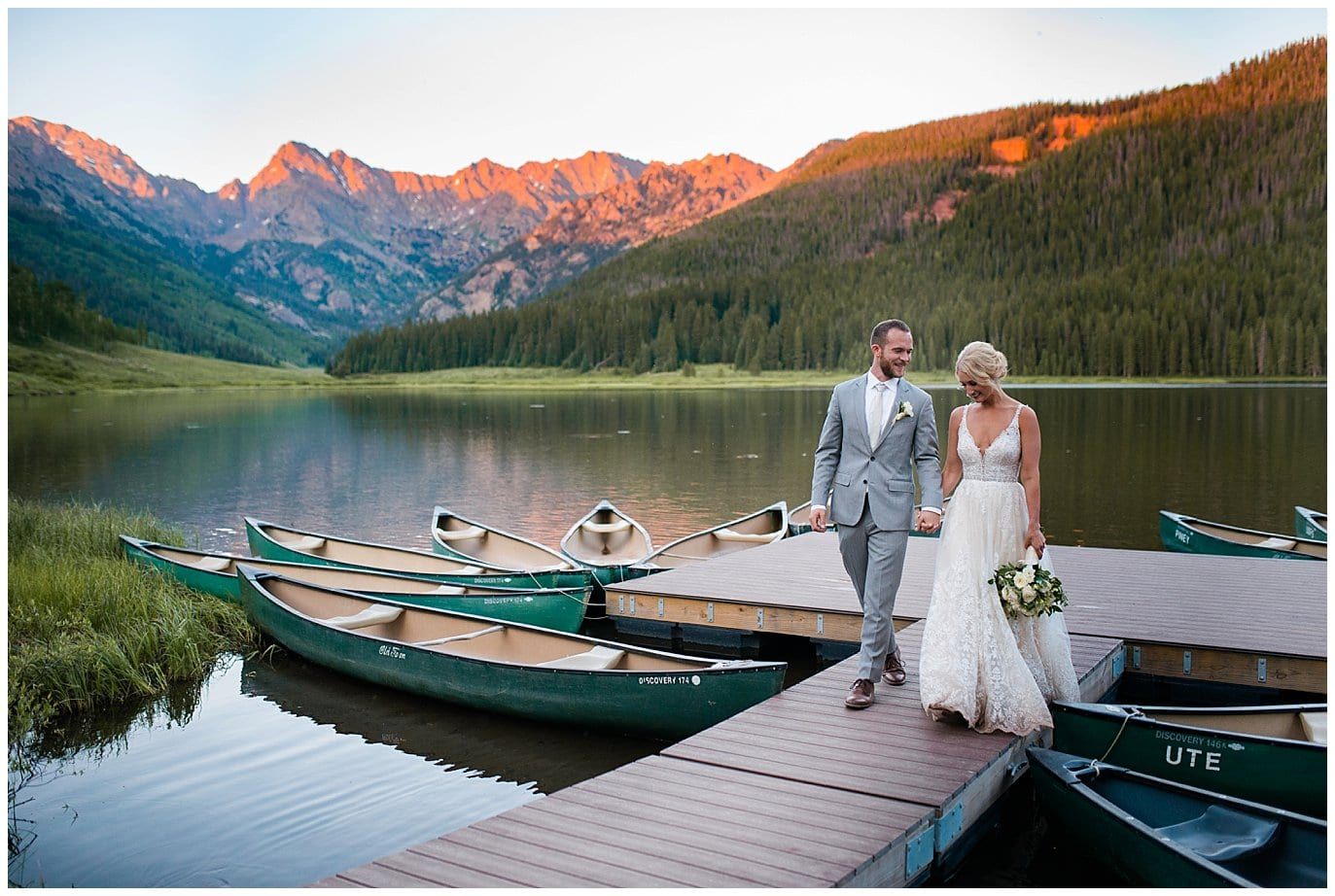 bride and groom walk on dock during sunset alpenglow at Piney River Ranch wedding by Vail wedding photographer Jennie Crate, Photographer