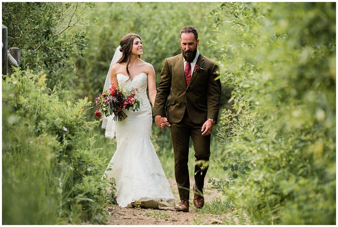 bride and groom walking in colorado aspens photo