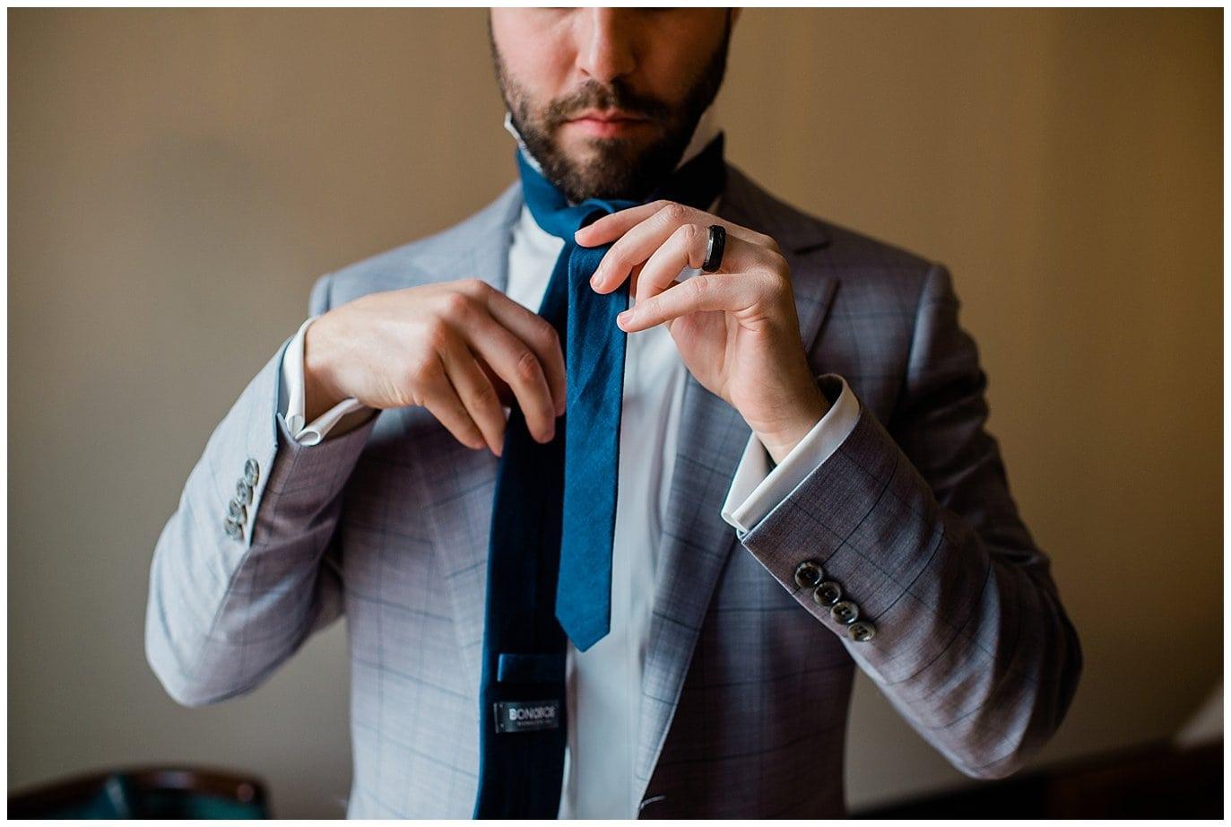 groom tying tie by Blanc Wedding Photographer Jennie Crate