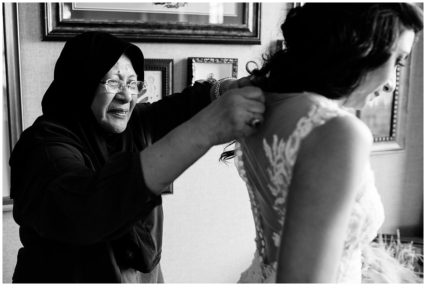 bride's mother helping her get dressed on wedding day by Blanc Wedding Photographer Jennie Crate