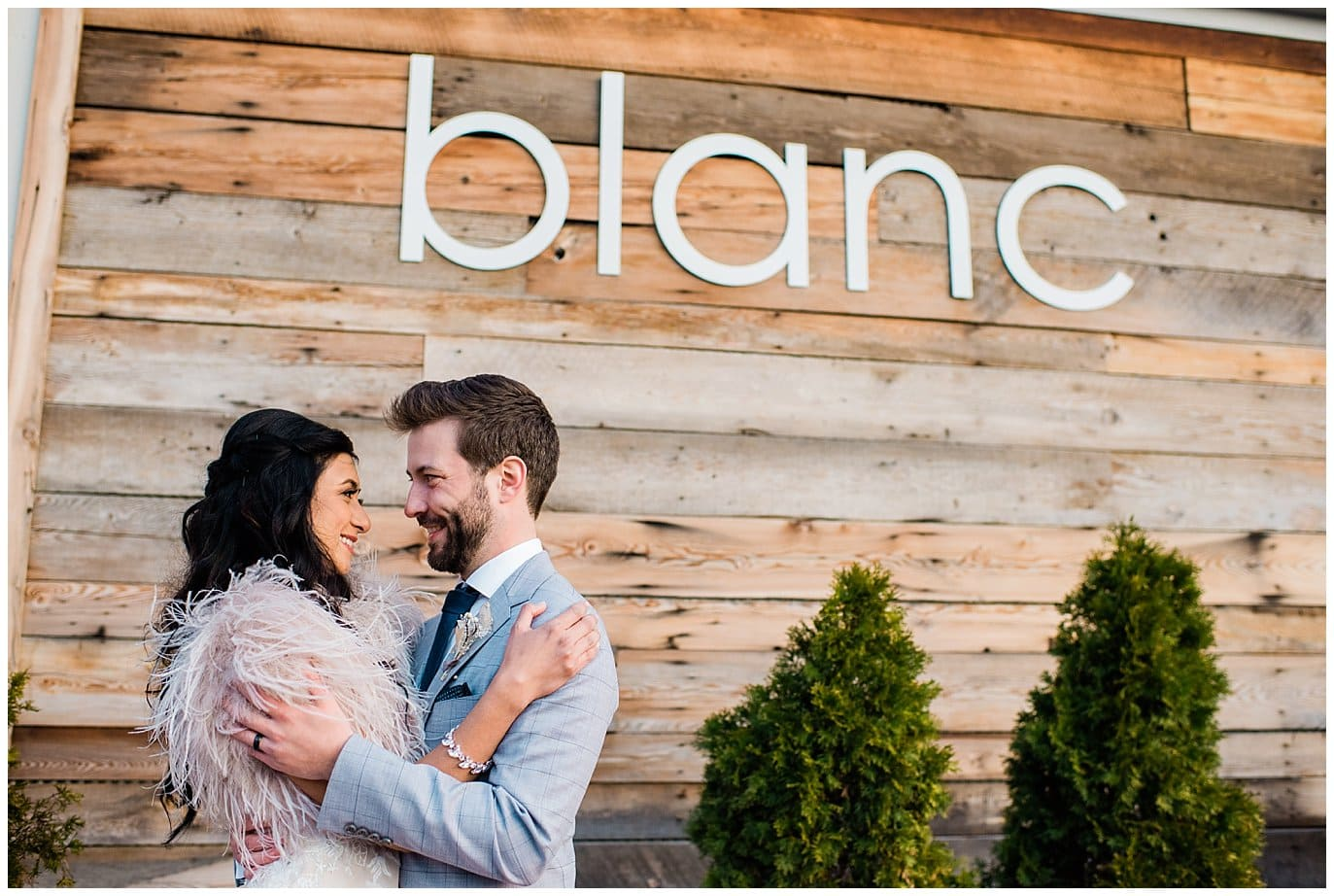 Bride and groom under blanc sign by Blanc Wedding Photographer Jennie Crate
