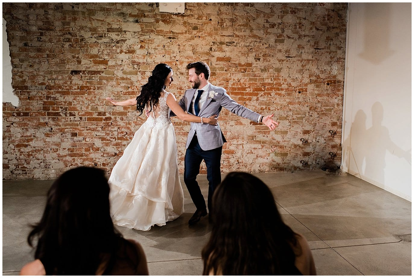 bride and groom dancing with brick wall at by Blanc Wedding Photographer Jennie Crate