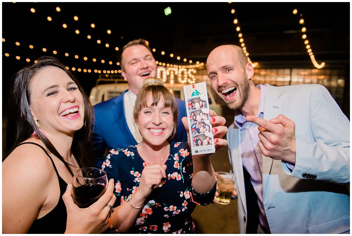 guests laughing at photo booth photos at Blanc Wedding by Jennie Crate